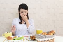 Woman with no appetite. Portrait of woman with no appetite in front of meals royalty free stock image