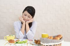Woman with no appetite. Portrait of woman with no appetite in front of the meal stock images