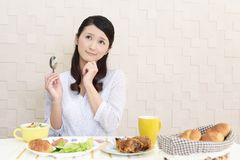Woman with no appetite. Portrait of woman with no appetite in front of the meal stock photos
