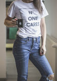 Woman in No One Cares Print White Crew Neck T-shirt and Blue Distressed Jeans Holding Black Ceramic Mug in Shallow Focus Photograp Stock Photo