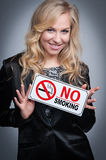 Woman With No Smoking Sign. Attractive blond woman holding a no smoking sign Royalty Free Stock Photo