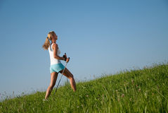 Woman nordic walking. Young goes woman nordic walking in her spare time in the nature Stock Photography