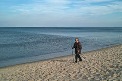 Woman Nordic walking on beach stock images