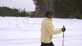 Woman nordic walking, healthy lifestylel. Trekking and hiking on winter landscape. Woman walks stock video