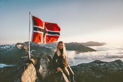 Woman and Norway flag on mountain summit. Blonde girl traveling enjoying view hiking adventure vacations outdoor active lifestyle royalty free stock image