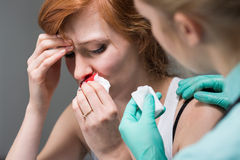 Woman with nosebleed and nurse Royalty Free Stock Photo