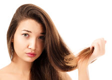 Woman is not happy with her fragile hair. White background, copyspace Stock Photography