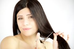 Woman not sure about cutting her long hair Stock Photo