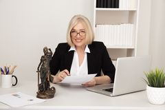 Woman notary at the desk infront of computer with documents. Statue of Justice. Woman notary at the desk infront of computer with documents. Statue of Justice royalty free stock image