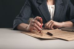Woman notary with paper documents and pen sitting at the desk. Woman notary with paper documents and pen sitting at the desk royalty free stock photos