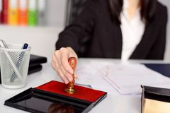 Woman notary public reaches her stamp Royalty Free Stock Photo