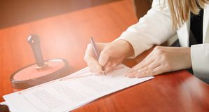 Woman Notary Public signing the contract. In her office. Law office Stock Photography