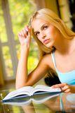 Woman with notebook. Portrait of beautiful young woman with notebook or organiser, indoors Royalty Free Stock Photography
