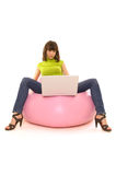 Woman with notebook. Woman sitting on comfortable chair and looking to the laptop Stock Images
