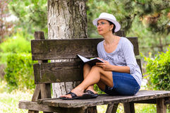 Woman with notebook on bench in park Royalty Free Stock Photo