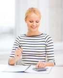 Woman with notebook and calculator studying Stock Images