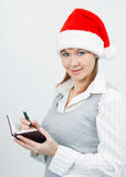 Woman with a notebook in a Christmas hat Stock Images