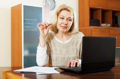 Woman with notebook and documents at home Stock Image