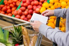 Woman with notebook in grocery store choosing vegetables, holding shopping list. Woman with notebook in grocery store choosing vegetables, holding shopping list Royalty Free Stock Photo