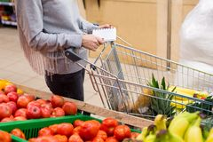 Woman with notebook in grocery store, closeup. Shopping list on paper. Stock Photos