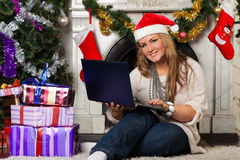 Woman with notebook near Christmas tree. Young woman with notebook sitting near Christmas tree at home Royalty Free Stock Image