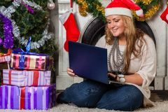 Woman with notebook near Christmas tree. Stock Images