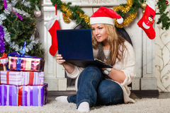 Woman with notebook near Christmas tree. Royalty Free Stock Photo