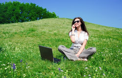 Woman with notebook and  phone sit on hill Royalty Free Stock Image
