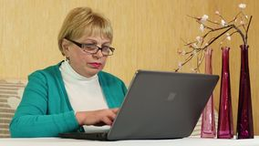 Woman with notebook. Senior woman types text using laptop stock video footage