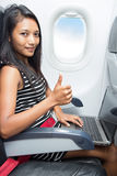 Woman with notebook sitting at airplane Royalty Free Stock Images