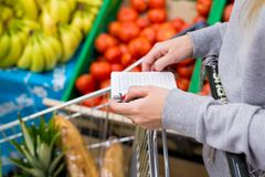 Woman with notebook in grocery store, closeup. Shopping list on paper. Woman with notebook in store, closeup. Shopping list on paper Royalty Free Stock Photography