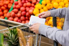 Woman with notebook in grocery store, closeup. Shopping list on paper. Woman with notebook in store, closeup. Shopping list on paper Stock Images