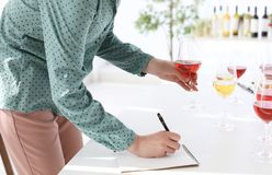 Woman with notebook tasting delicious wine. At table indoors royalty free stock images