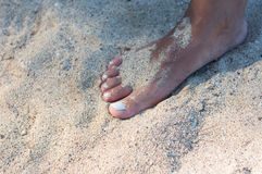 Woman& nudo x27; piede di s sulla spiaggia sabbiosa Fotografie Stock Libere da Diritti