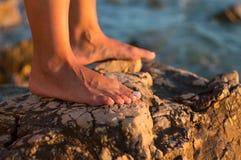Woman& nudo x27; piedi di s sulla spiaggia rocciosa Fotografia Stock
