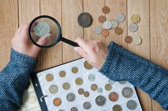 Woman-numismatist views coins from a coin album through a magnifying glass. Top view stock image