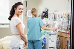 Woman With Nurse Examining Patient In Hospital Stock Photo