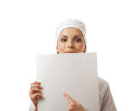 Woman nurse showing blank sign board, isolated. Royalty Free Stock Photography