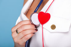 Woman in nurse suit with stetoscope red heart. Red heart woman in nurse suit with stethoscope blue background Royalty Free Stock Images