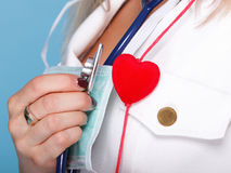 Woman in nurse suit with stetoscope red heart. Red heart woman in nurse suit with stethoscope blue background Royalty Free Stock Photography