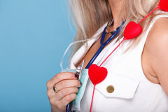 Woman in nurse suit with stetoscope red heart. Red heart woman in nurse suit with stethoscope blue background Stock Image