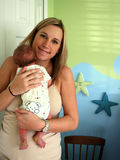 Woman In Nursery. A sandy colored hair woman standing with a newborn baby held close to her chest, a closed mouth smile on her face, in a nursery with blue and Stock Photos