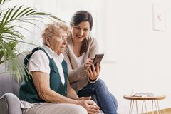Woman in nursing home with her granddaughter showing her how to use a mobile phone stock images