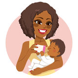 Woman Nurturing Baby Bottle Milk. African American young beautiful woman nurturing her little baby with milk bottle Royalty Free Stock Photography