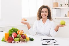 Woman nutritionist holding fruit and croissant in hands royalty free stock photos