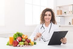Woman nutritionist showing blank clipboard at office stock images