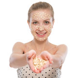 Woman with oatmeal facial mask showing oatmeal royalty free stock photos
