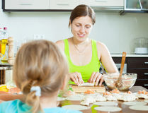 Woman with an obedient child making fish salmon dumplings Stock Photography