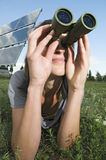 Woman observe on the grass. Woman lying in the grass next to solar panels with binoculars Stock Photo