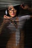 Woman observes peep at jalousie Royalty Free Stock Photography